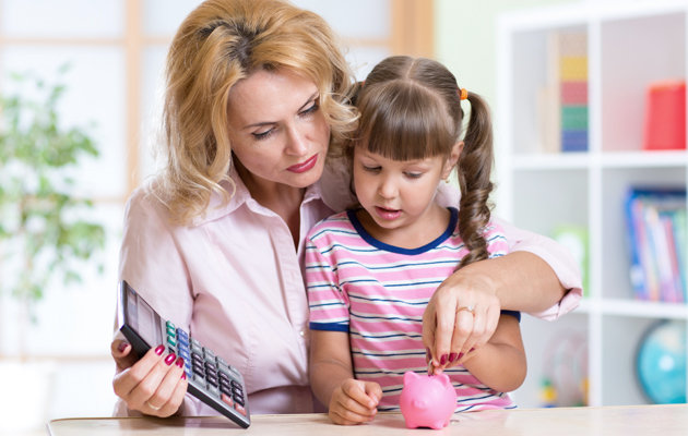 Mom is showing her daughter how to make use of piggy bank with a calculator in her hand